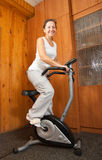 Woman workout on stationary bicycle Royalty Free Stock Images