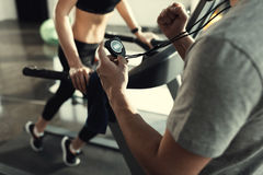 Woman workout on treadmill and trainer with timer Royalty Free Stock Images