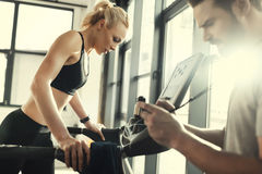Woman workout on treadmill and trainer with timer, side view Royalty Free Stock Photo