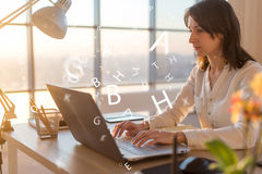 Woman at workplace using laptop working, typing, surfing the internet stock photos