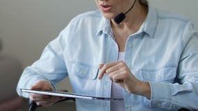Woman works as freelance consultant at home, using tablet and headset microphone stock video