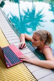 A woman works on the computer in the pool. stock photos