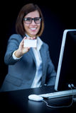 Woman works at the computer and showing a card Royalty Free Stock Photos