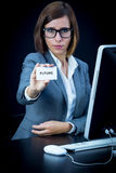 Woman works at the computer and showing a card with text Stock Photos
