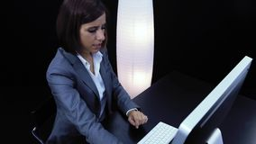 Woman works at the computer and showing a card with text. Woman works at the computer and showing a card with question mark sign stock footage