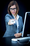 Woman works at the computer and showing a card with text Royalty Free Stock Photo
