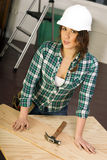 Woman Works on Construction Project Plywood Hardhat Tools Hammer stock photos