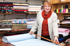 Woman  works at  fabric store. Mature woman  works at  fabric store Royalty Free Stock Photography