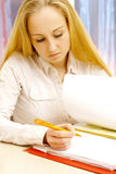 Woman works with her papers. Royalty Free Stock Image