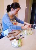 Woman works in kitchen. Woman preparing layer salad in kitchen Royalty Free Stock Photography