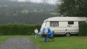 A woman works on laptop under blue umbrella under rain in camping near trailer stock video footage