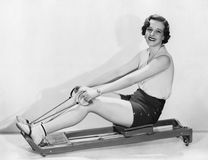 Woman works out on rowing machine