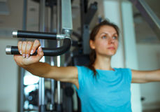 Woman works out on training apparatus in fitness center. Athletic woman works out on training apparatus in fitness center Royalty Free Stock Image