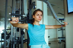 Woman works out on training apparatus in fitness center. Athletic woman works out on training apparatus in fitness center Stock Photography