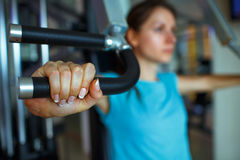 Woman works out on training apparatus in fitness center. Athletic woman works out on training apparatus in fitness center Royalty Free Stock Images
