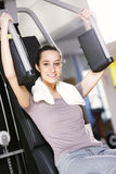 Woman works out on weight-training machine Stock Images