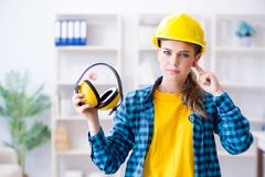 The woman in workshop with noise cancelling headphones. Woman in workshop with noise cancelling headphones stock images