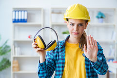The woman in workshop with noise cancelling headphones. Woman in workshop with noise cancelling headphones stock image