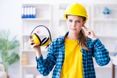 The woman in workshop with noise cancelling headphones. Woman in workshop with noise cancelling headphones stock photos