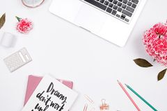 Woman workspace with laptop, handwritten quote notebook, pink ca royalty free stock image