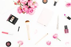 Woman workspace with pink roses bouquet, cosmetics, diary on white background. Top view. Flat lay home feminine desk. Beauty or fa. Woman workspace with pink Royalty Free Stock Photography
