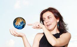 Woman and world. Young woman with levitate world on sky background Stock Photo