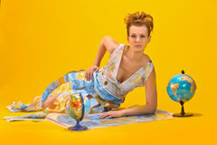 Woman with a world map and globes Stock Photo