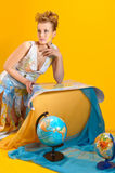 Woman with a world map and globes Stock Image