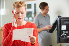Woman Worried By TV Repair Bill Royalty Free Stock Photos