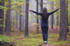 Woman worshiping with open arms in an autumn misty forest with yellow, green and red leaves.  Royalty Free Stock Images