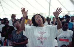 Woman worships and prays intensely at a tent revival royalty free stock images
