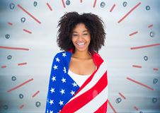 Woman wrapped in american flag against blurry blue wood panel and red blue fireworks doodle Stock Photography
