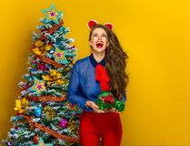 Woman with wrapped as a gift photo camera looking at copy space. Festive season. smiling young woman near Christmas tree isolated on yellow background with Stock Image