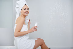 Woman Wrapped with Bath Towels, Applying Cream on her Face Royalty Free Stock Photos