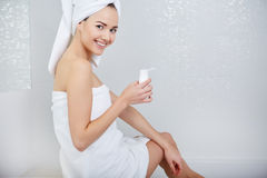 Woman Wrapped with Bath Towels, Applying Cream on her Face Royalty Free Stock Images