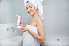 Woman Wrapped with Bath Towels, Applying Cream on her Face Stock Photos