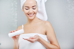 Woman Wrapped with Bath Towels, Applying Cream on her Face Royalty Free Stock Photo