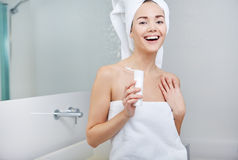 Woman Wrapped with Bath Towels, Applying Cream on her Face Royalty Free Stock Image