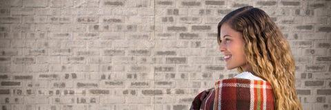 Woman wrapped in blanket against brown brick wall. Digital composite of Woman wrapped in blanket against brown brick wall Royalty Free Stock Photo