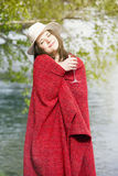Woman wrapped in blanket holding a glass of champagne outdoors Royalty Free Stock Images