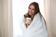 Woman wrapped in a blanket and holds a mug after wake up, entering a day happy and relaxed after good night sleep. Sweet Stock Image