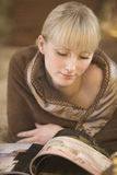 Woman Wrapped In Blanket Looking At Magazine Royalty Free Stock Photos
