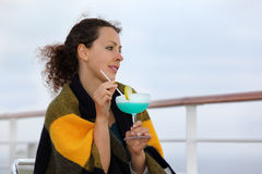 Woman wrapped in blanket sits on cruise liner deck. Smiling woman wrapped in blanket sits on chair on cruise liner deck, dreams and holds cocktail Stock Photos