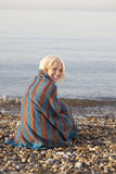 Woman Wrapped In Blanket Sitting At Beach Stock Photos