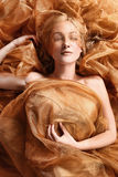 Woman Wrapped in Copper Flowing Fabric Royalty Free Stock Photography