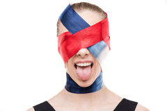Woman with wrapped face with ribbons sticking tongue out Royalty Free Stock Photography