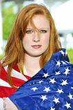 Woman Wrapped in a Flag. A beautiful young woman wrapped in a flag Royalty Free Stock Images