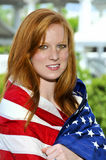Woman Wrapped in a Flag. A beautiful young woman wrapped in a flag Royalty Free Stock Photos