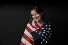 Woman Wrapped in a Flag. A beautiful young woman wrapped in a flag Stock Image