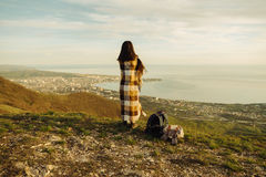 Woman wrapped in plaid standing on peak of mountain Royalty Free Stock Photography